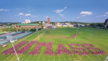 People in dressed in maroon organized into groups to spell UMass on a field