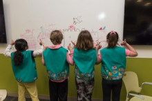 Girl Scouts in uniform drawing on a white board