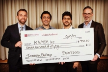 Four person Kinase Inc. Team holding novelty check
